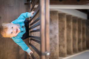DSLR picture of a baby boy holding the stair gate.